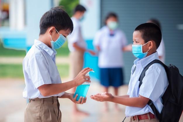 Asiatische grundschüler tragen sie eine medizinische maske, um eine infektion mit dem coronavirus zu verhindern