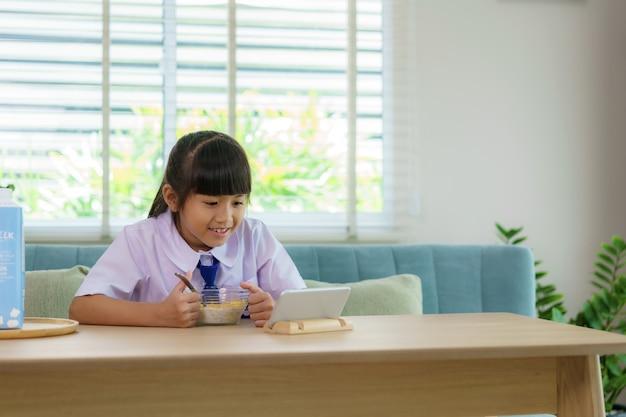 Asiatische grundschülerin in uniform, die frühstückszerealien mit milch isst und karikatur im smartphone schaut