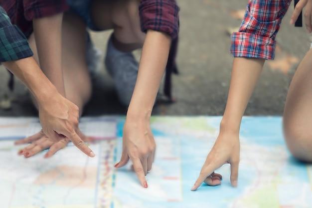 Asiatische gruppe, die mit den freundrucksäcke zusammen gehen wandert und karte schaut