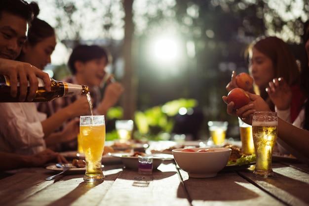 Asiatische gruppe, die nachts vor dem haus kaltes bier isst und trinkt