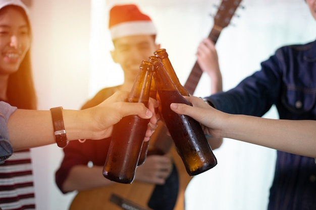 Asiatische gruppe freunde, die partei mit alkoholischen biergetränken haben und junge leute, die an einer bar cocktails rösten