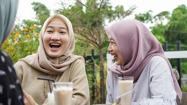 Asiatische gruppe hijab frau, die im café mit freund lächelt