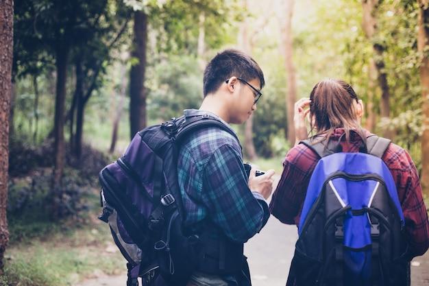 Asiatische gruppe junge leute, die mit den freundrucksäcken wandern zusammen wandern