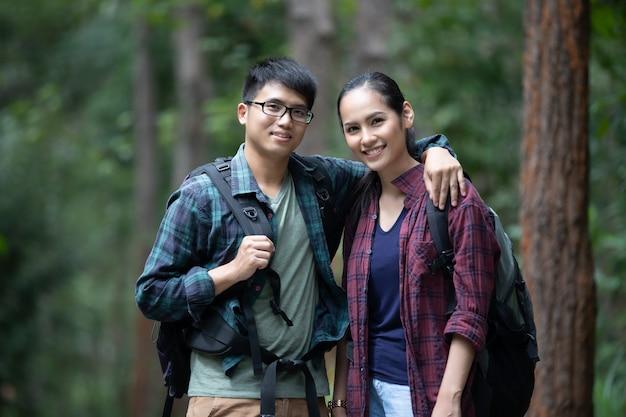 Asiatische gruppe junge leute, die mit gehender reise der freundrucksäcke am feiertag wandern
