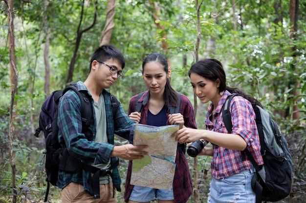 Asiatische gruppe von jungen leuten, die mit freundrucksäcken wandern, die zusammen gehen und karte suchen