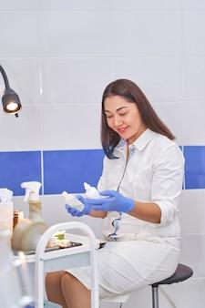 Asiatische gynäkologin ärztin im weißen kittel schaut in den rahmen.