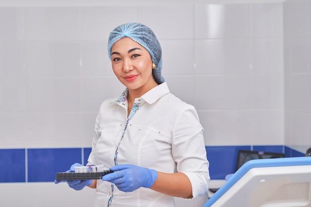 Asiatische gynäkologin in einem weißen kittel mit tests.