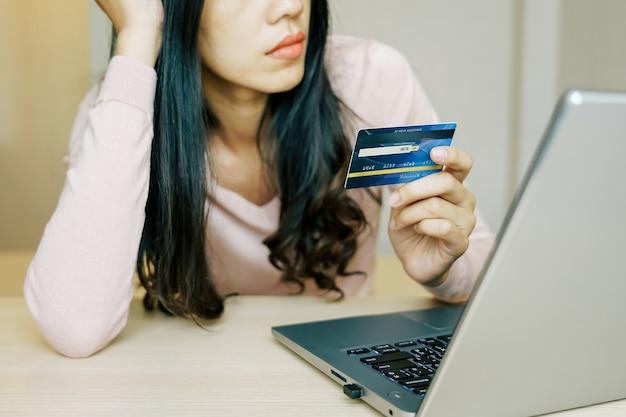 Asiatische hände der jungen frau, die kreditkarte halten und laptop smartphone verwenden