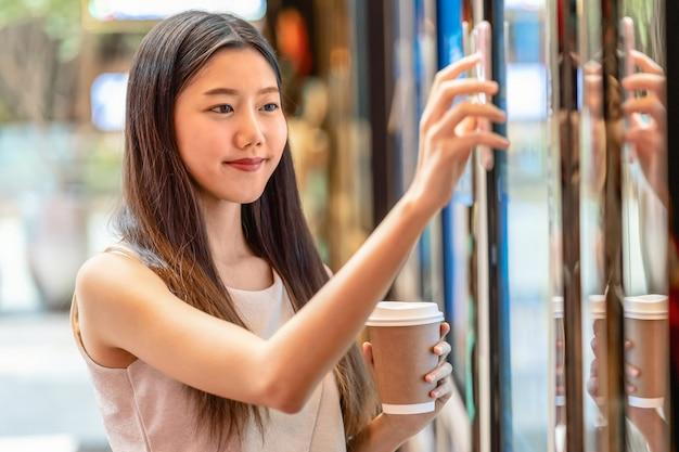 Asiatische hand der jungen frau, die den intelligenten handy scannt die kinokartenmaschine für kauf verwendet und erhält den kupon im kaufhaus-, lebensstil- und freizeit-, unterhaltungs- und technologiescannerkonzept