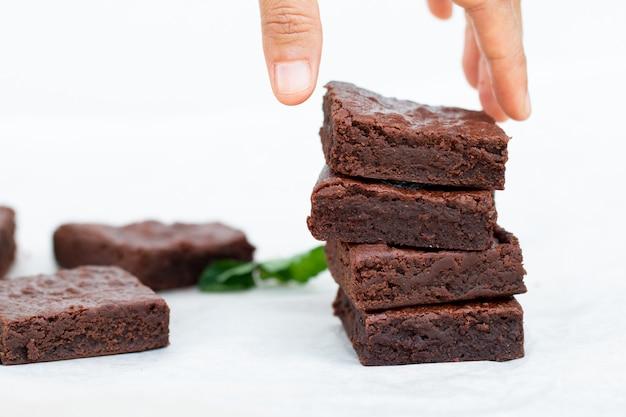 Asiatische hand, die einen schokoladen-schokoladenkuchen auswählt
