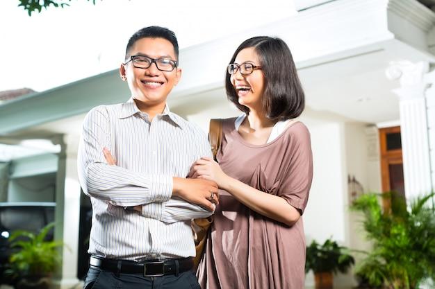 Asiatische hausbesitzerpaare vor haus