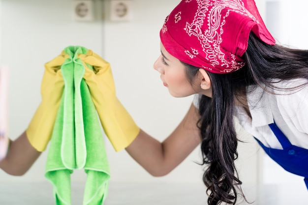 Asiatische hausfrau, die das haus mit einem tuch reinigt