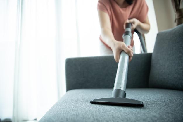 Asiatische hausfrau, die eine drahtlose staubsaugermaschine verwendet, um ein sofa im wohnzimmer aus nächster nähe zu reinigen. asiatische haushälterin, die im wohnzimmer staubsaugt. hausarbeit und tägliche hausarbeit-aktivitäten-konzept.
