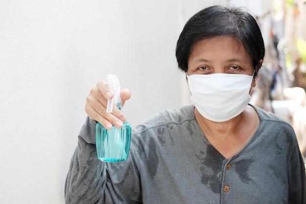 Asiatische haushälterin mit weißer maske verhindert covid-19- oder corona-virus und luftverschmutzungswert pm 2,5