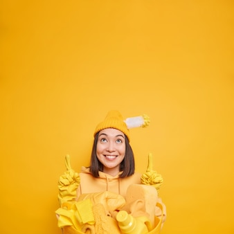 Asiatische hausmeisterin zeigt oben auf leerzeichen reinigungsmittel im wäschekorb und zeigt das beste produkt für die hauswirtschaft trägt hutgummihandschuhe isoliert auf gelber wand