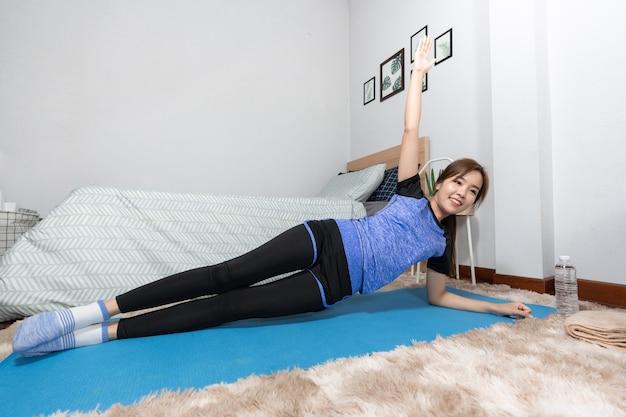 Asiatische heimfitness und yoga auf einer fitnessmatte, die übung macht