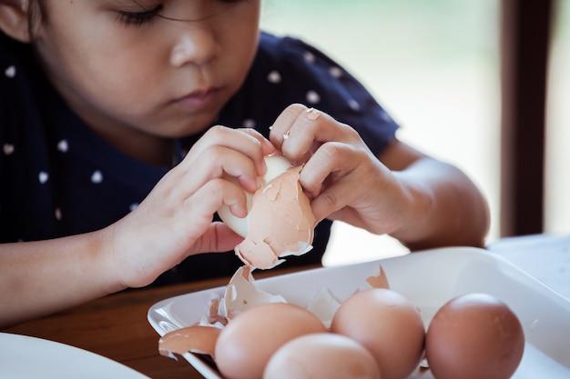 Asiatische helfende mutter des kleinen mädchens, zum eines eies zu schälen