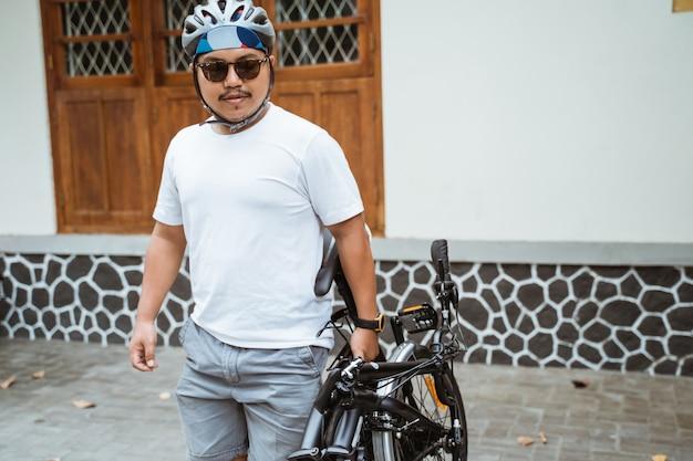 Asiatische herrensonnenbrille hält sein faltrad, um sich auf die arbeit vorzubereiten