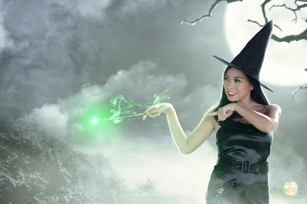 Asiatische hexenfrau, die den stab mit magischem glanz verwendet