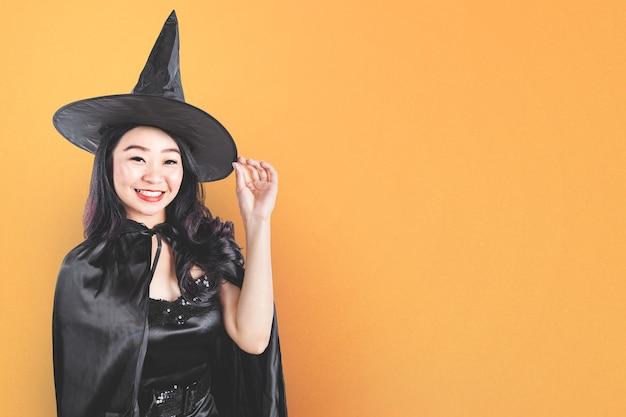 Asiatische hexenfrau mit einem hut, der mit einem farbigen hintergrund steht