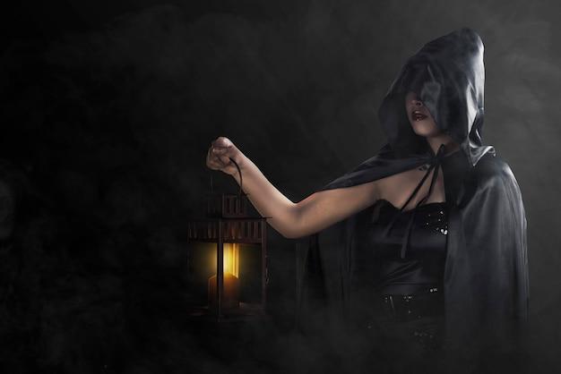 Asiatische hexenfrau mit einem schwarzen umhang, der eine laterne hält, die mit dunkler wand steht