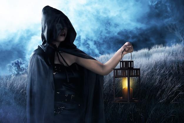 Asiatische hexenfrau mit schwarzem mantel, die eine laterne hält, die auf dem feld steht