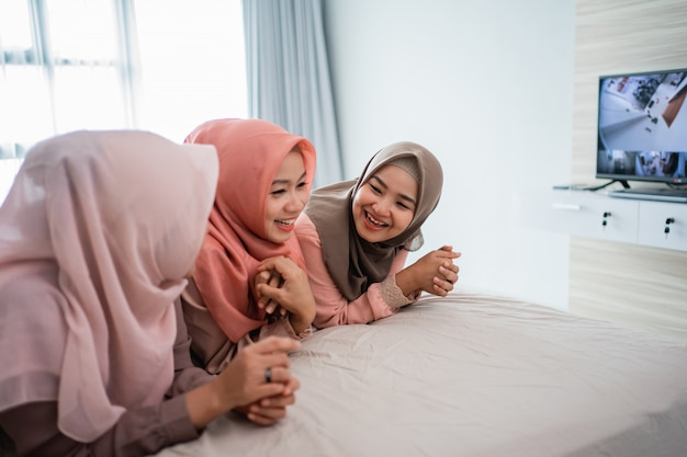 Asiatische hijab-frau, die lügt und genießt, auf dem bett zu plaudern