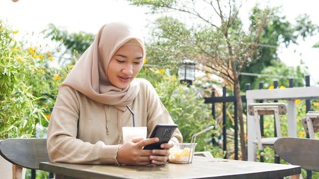 Asiatische hijab-frau, die telefon im café spielt