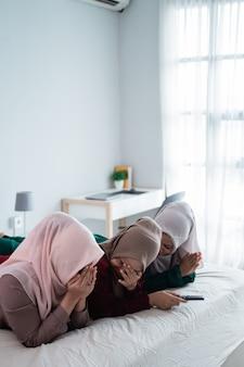 Asiatische hijab-frau mit freunden bedecken gesicht wegen der angst beim horor-film
