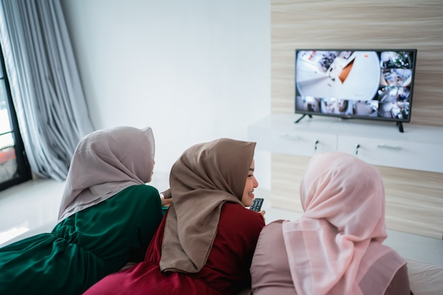 Asiatische hijab-frau mit freunden, die auf dem bett liegen, genießen das fernsehen
