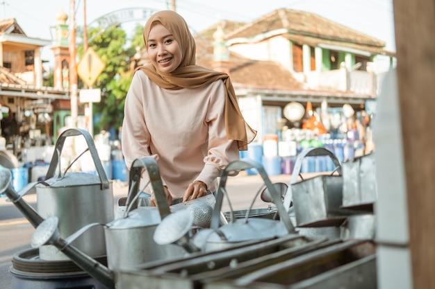 Asiatische hijab-frau steht bei der auswahl der gießkanne vor dem haushaltsgeräte-laden