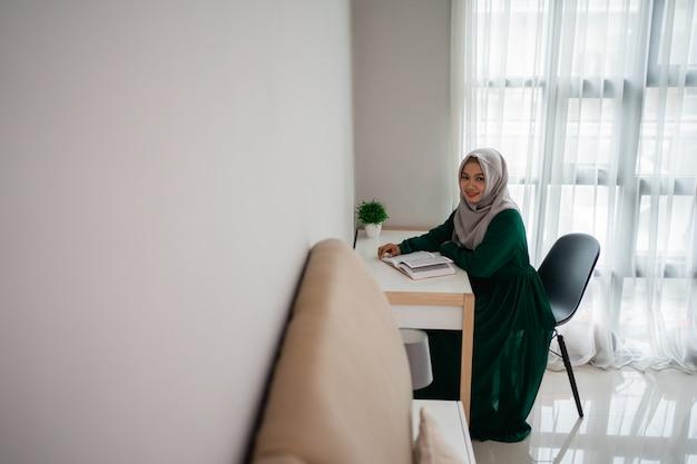 Asiatische hijab-frauen lächeln, wenn sie auf dem stuhl sitzen und das heilige buch al-quran lesen