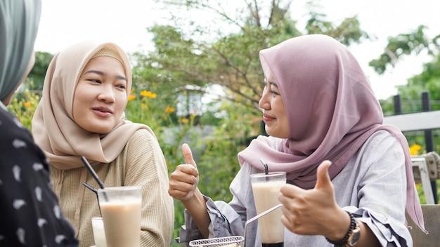 Asiatische hijab-frauengruppe, die im café mit freund lächelt