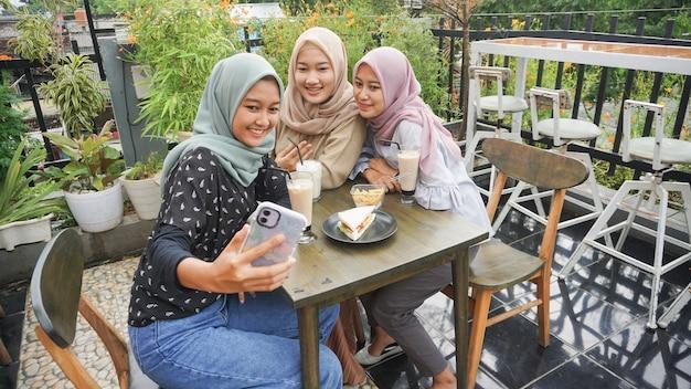 Asiatische hijab-frauengruppen-selfie im café mit freund