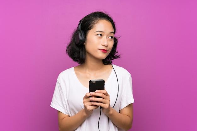 Asiatische hörende musik des jungen mädchens mit einem mobile über lokalisierter purpurroter wand