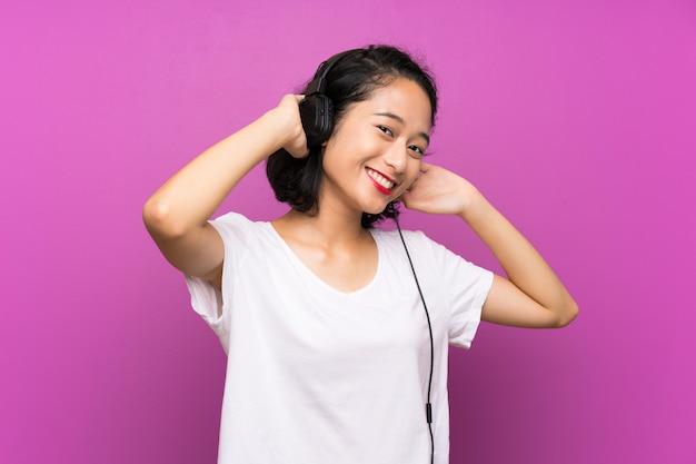 Asiatische hörende musik des jungen mädchens mit einem mobile über purpurroter wand
