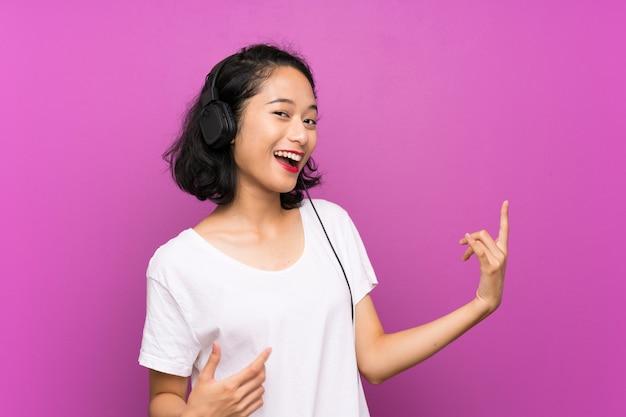 Asiatische hörende musik des jungen mädchens mit einem mobile und einem tanzen