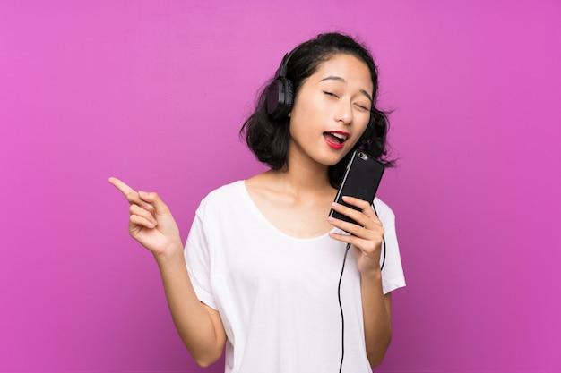 Asiatische hörende musik des jungen mädchens mit einem mobile und gesang über lokalisierter purpurroter wand