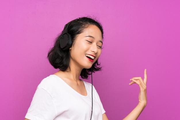 Asiatische hörende musik des jungen mädchens mit einem mobile und tanzen über purpurrote wand