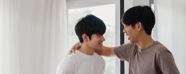 Asiatische homosexuelle paare, die zu hause nahe dem fenster stehen und umarmen. die jungen asiatischen lgbtq + männer, die glücklich küssen, entspannen sich rest verbringen zusammen romantische zeit im wohnzimmer am modernen haus morgens.