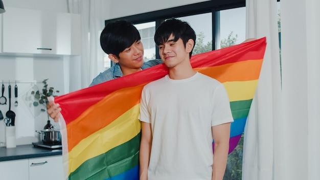 Asiatische homosexuelle paare, die zu hause raum stehen und umarmen. die jungen hübschen lgbtq + männer, die glücklich küssen, entspannen sich rest verbringen zusammen romantische zeit in der modernen küche mit regenbogenflagge am haus morgens.