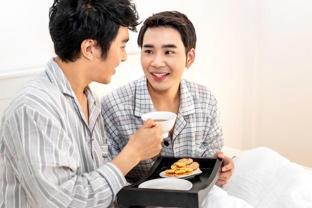 Asiatische homosexuelle paare in den pyjamas, die im bett frühstücken. konzept lgbt-homosexuell.
