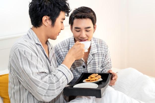 Asiatische homosexuelle paare in den pyjamas, die im bett frühstücken