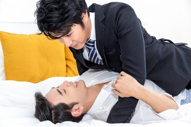 Asiatische homosexuelle paare in der liebe, die einander untersucht, mustert im bett