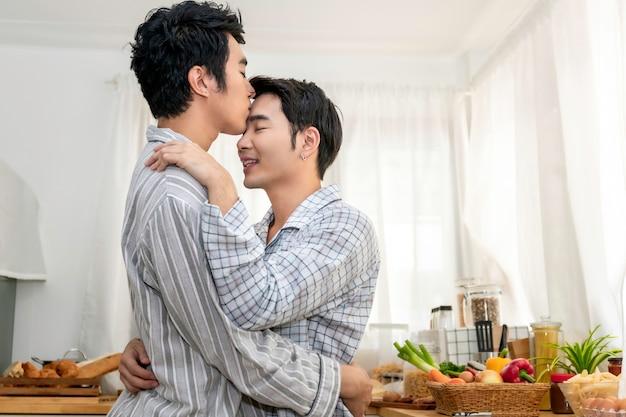 Asiatische homosexuelle paare umarmen und küssen an der küche morgens