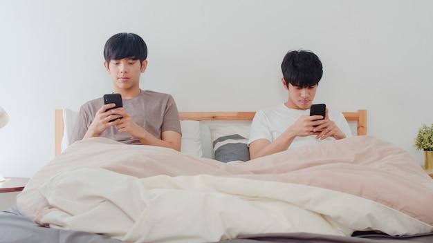 Asiatische homosexuelle paare unter verwendung des handys zu hause. junge asiatische lgbtq + männer, die glücklich sind, entspannen sich rest zusammen, nachdem sie aufwachen, überprüfen das social media, das morgens auf bett im schlafzimmer zu hause liegt.