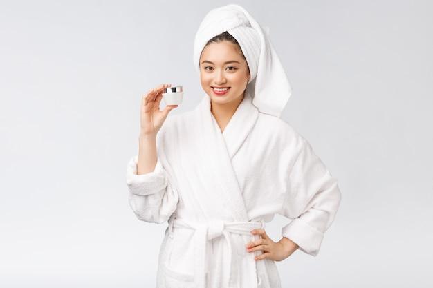 Asiatische hübsche frau des schönheitskonzepts mit perfekter haut, die kosmetische flasche hält