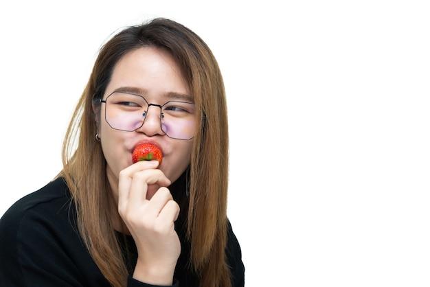 Asiatische hübsche frau, die frische erdbeere hält und isst, ist rote beerenfruchtfarbe und süß saftig mit genuss und glücklicher emotion im konzeptlebensmittel, gesundes essen im leben
