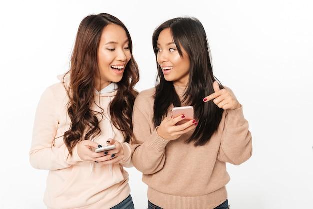 Asiatische hübsche glückliche damenschwestern, die durch handys plaudern.