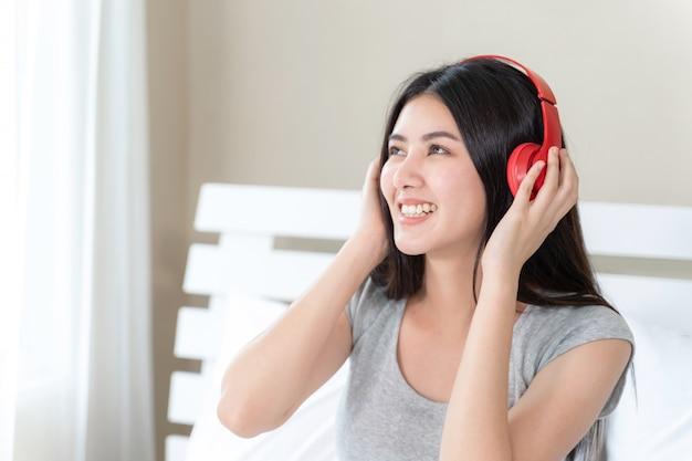 Asiatische hübsche jugendfrau, die roten bluetooth kopfhörer, tanz und smiley für hörende musik mit fröhlichem trägt